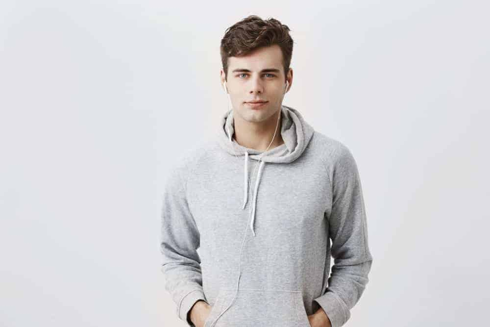A man wearing a gray hoodie with drawstring.