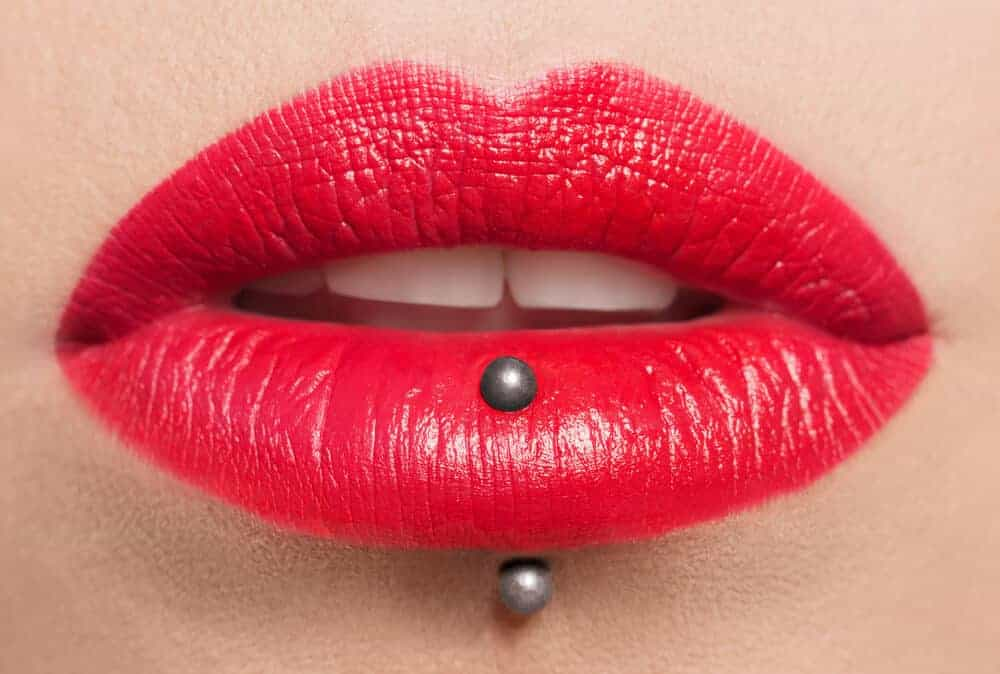 A vertical labret piercing on a woman wearing a cool-tone red lipstick.