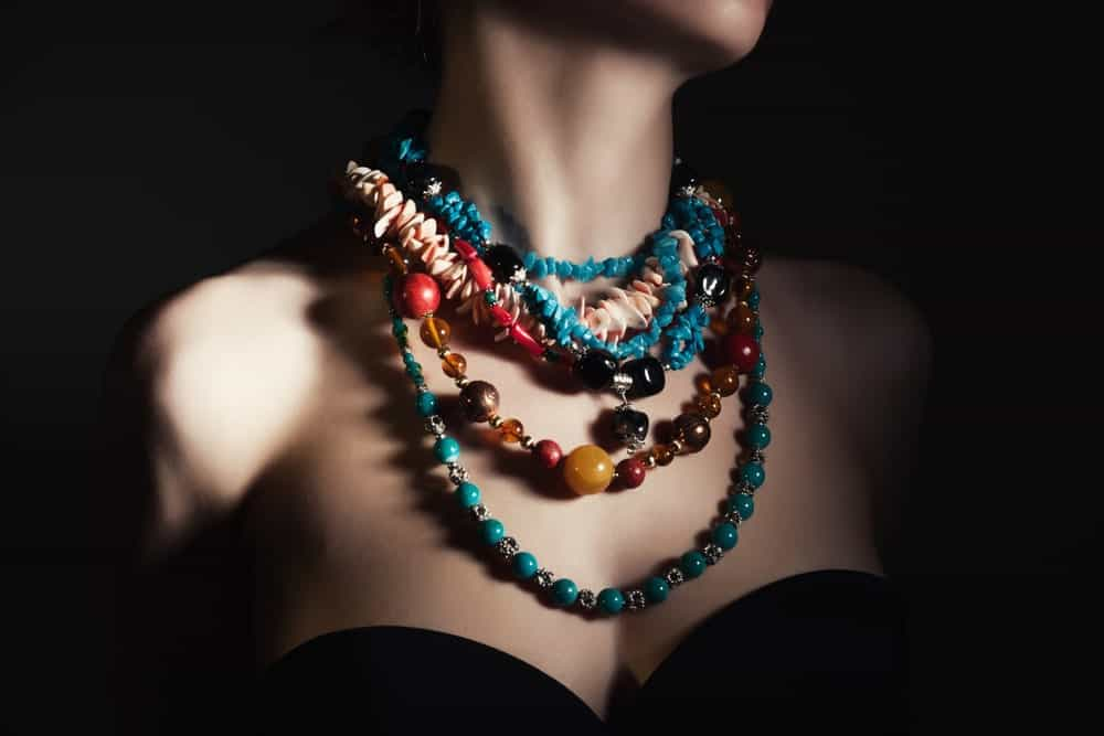 A close look at a woman wearing various bead necklaces.