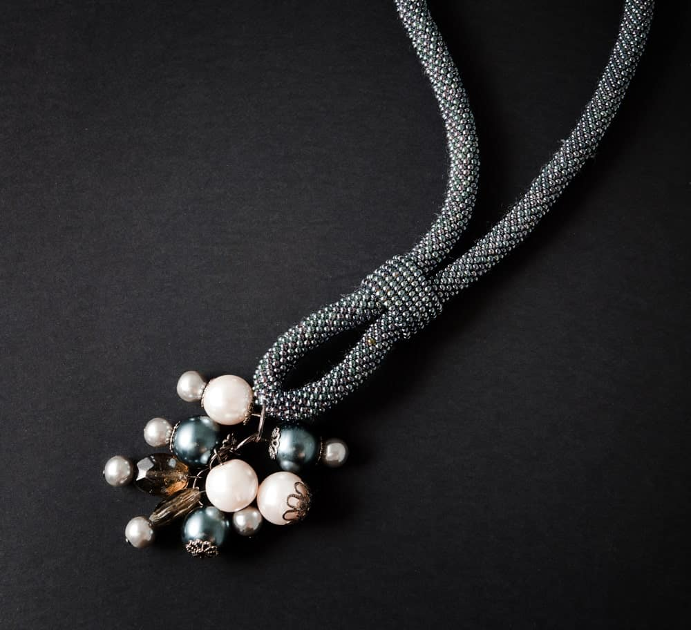 A string necklace with pearls for a pendant.