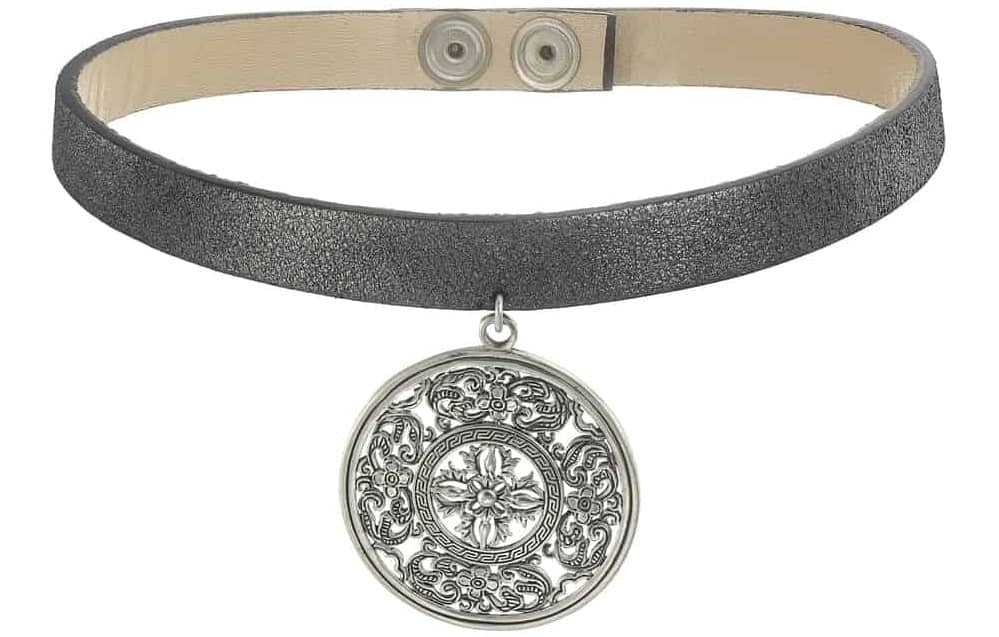 A close look at a leather necklace with a medallion pendant.