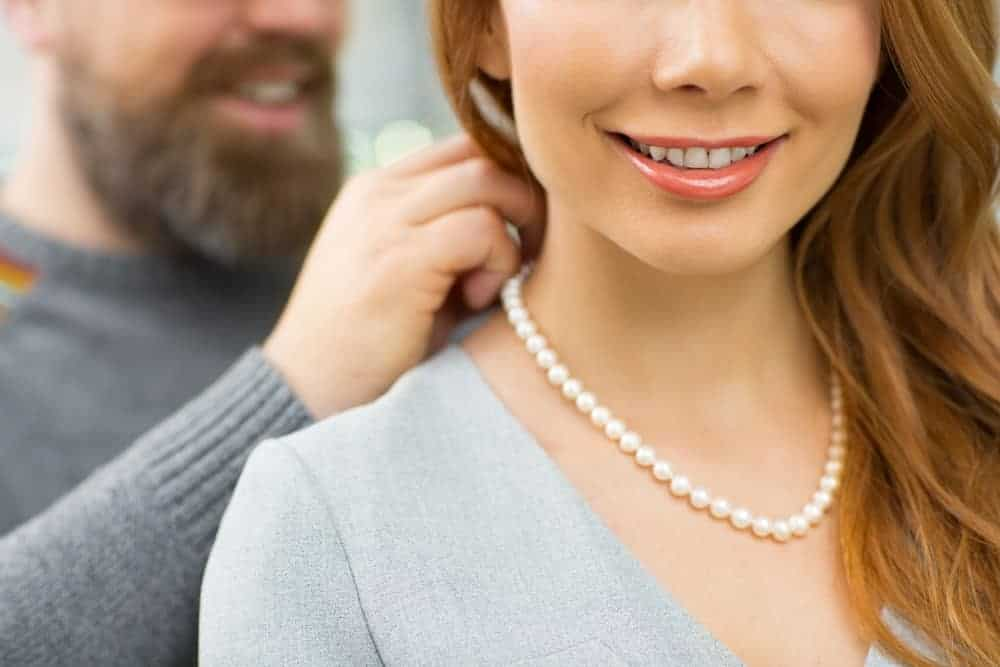 A lady wearing a pearl necklace.