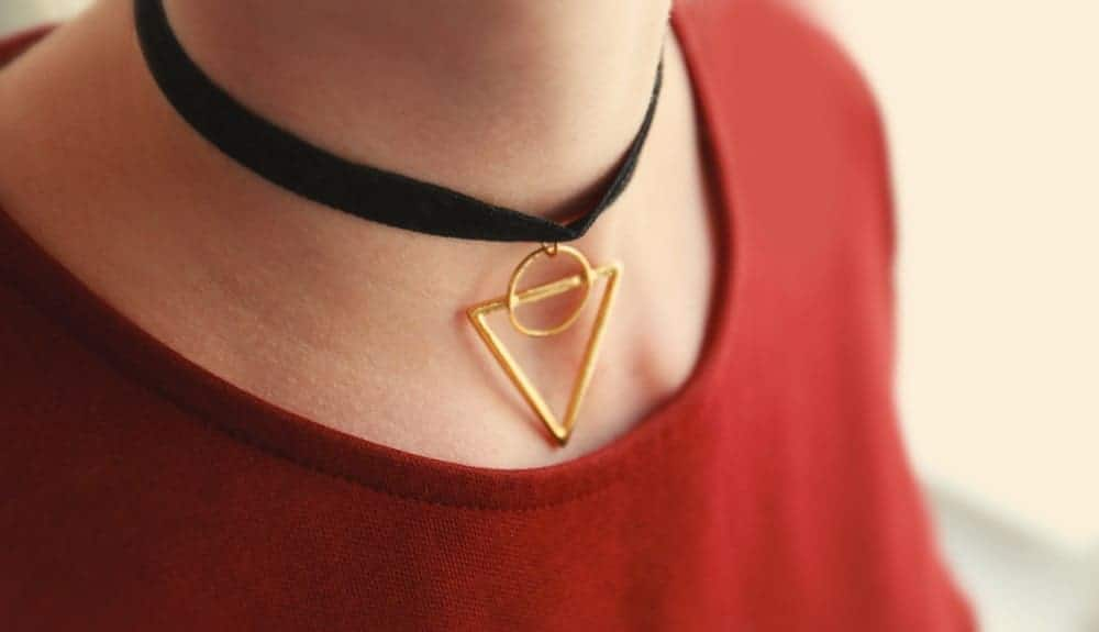 A woman wearing a choker with gold triangle.