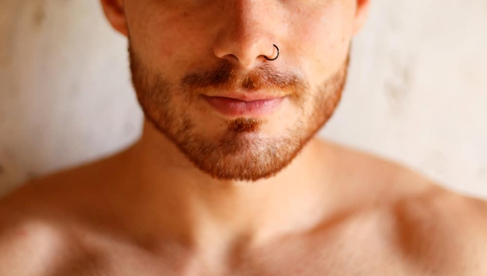 A close look at a man with a nose piercing.