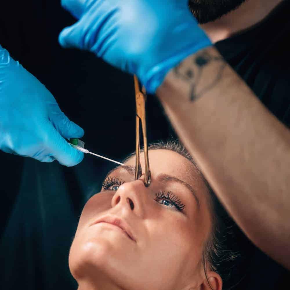 Woman undergoing a nose bridge piercing.