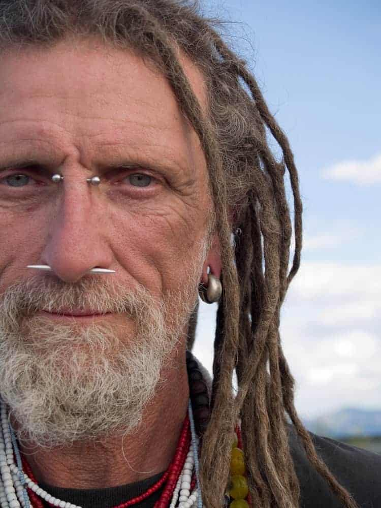 Eccentric man with nose piercings and dreadlocks.