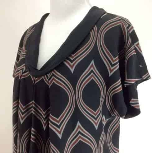 Black blouse with rolled collar.