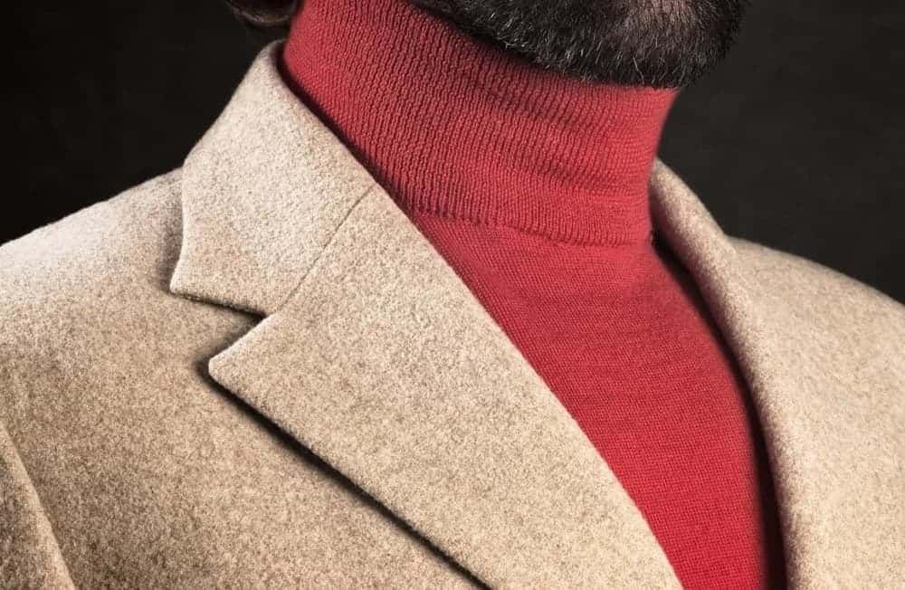 Closeup of a red turtleneck shirt under a brown suit.