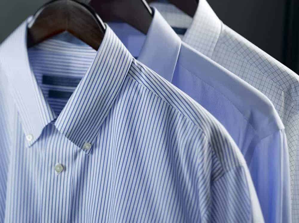 Three long sleeve shirts with button down collar on wooden clothes hanger.