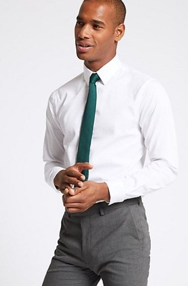 Man wearing a white long sleeves shirt with forward point collar and green tie.