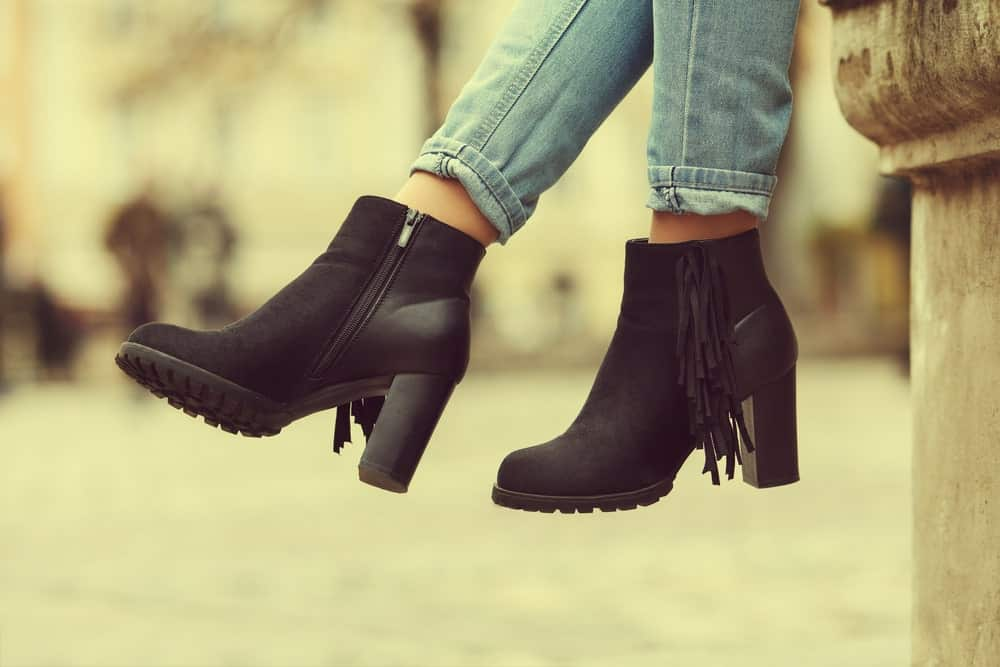 A close look at a woman wearing a pair of ankle booties.