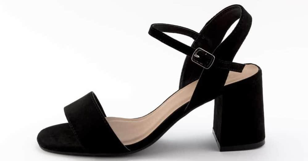 A close look at a black block heel shoe.