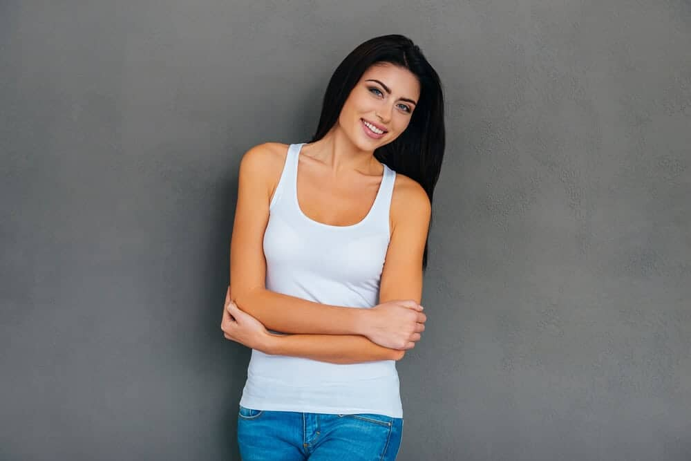 Woman with long, black hair wearing a white tank top.
