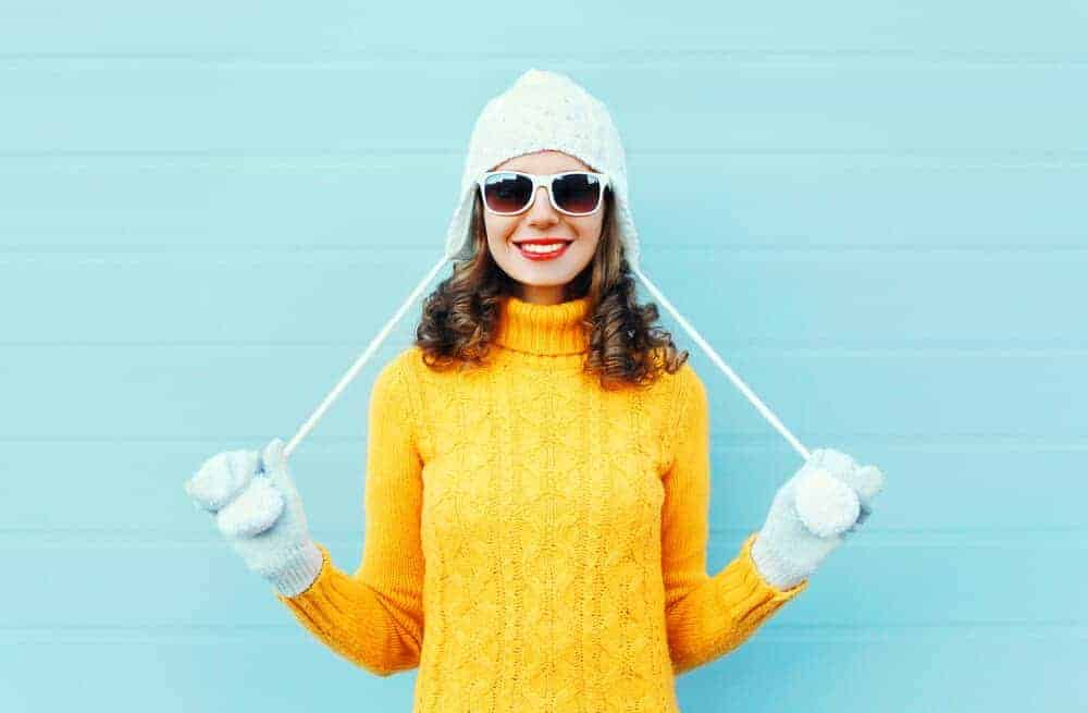A woman having fun with her bright yellow winter top.