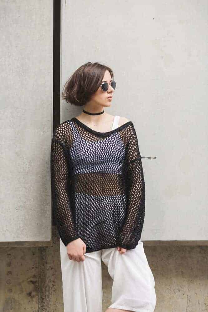 Cropped tank top inside a fashionable black net top.