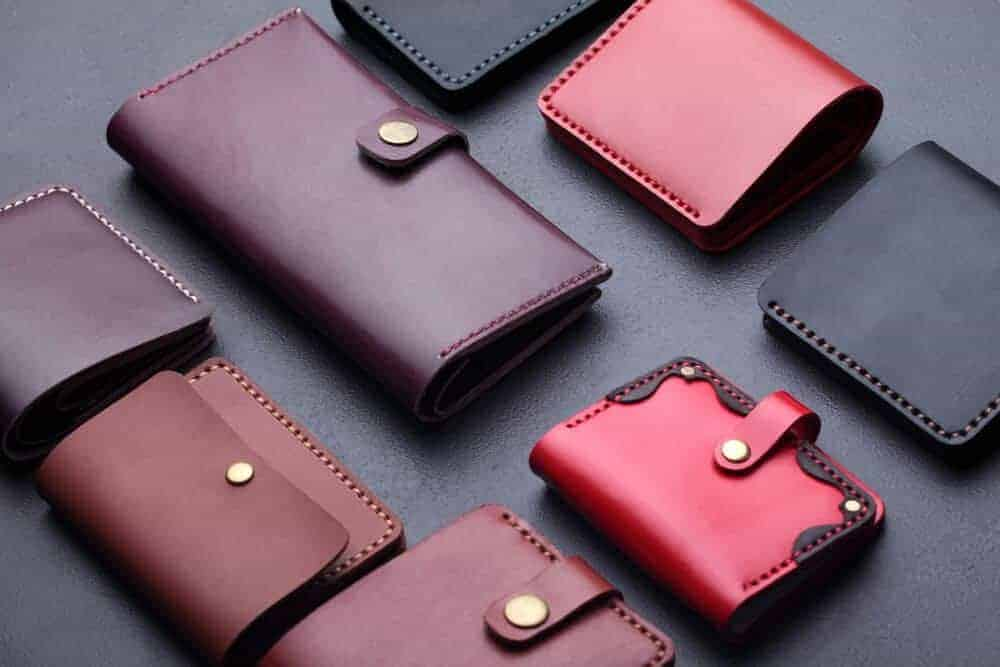An assortment of leather wallets on a dark surface.
