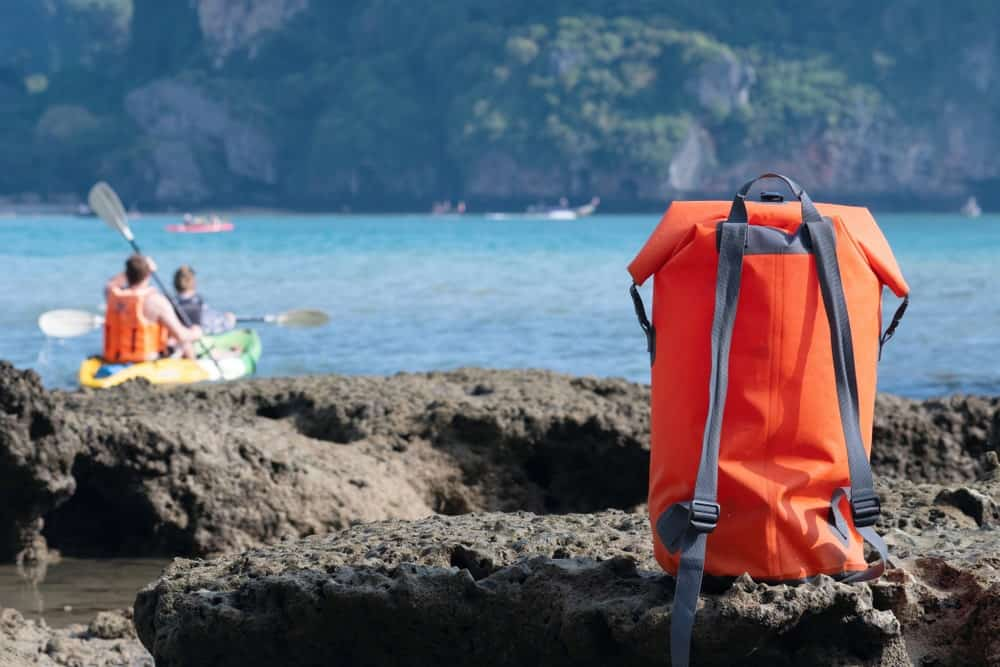 An orange waterproof backpack sitting on large stones near the sea.