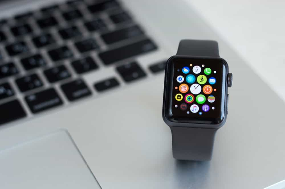 An Apple watch with gray straps on a laptop.