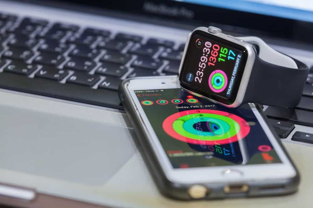 An Apple Watch and an Iphone on a laptop.