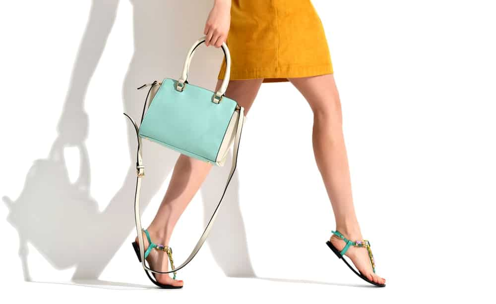 Woman's legs in yellow skirt and summer sandals along with a blue mint clutch bag.