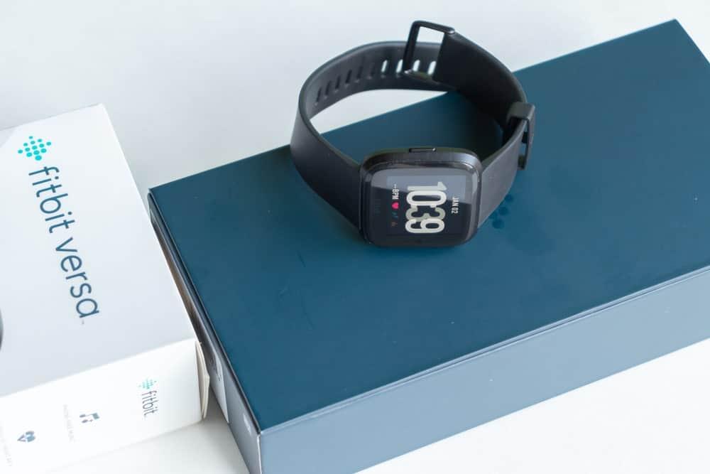 Black Fitbit versa smartwatch on top of its original box.
