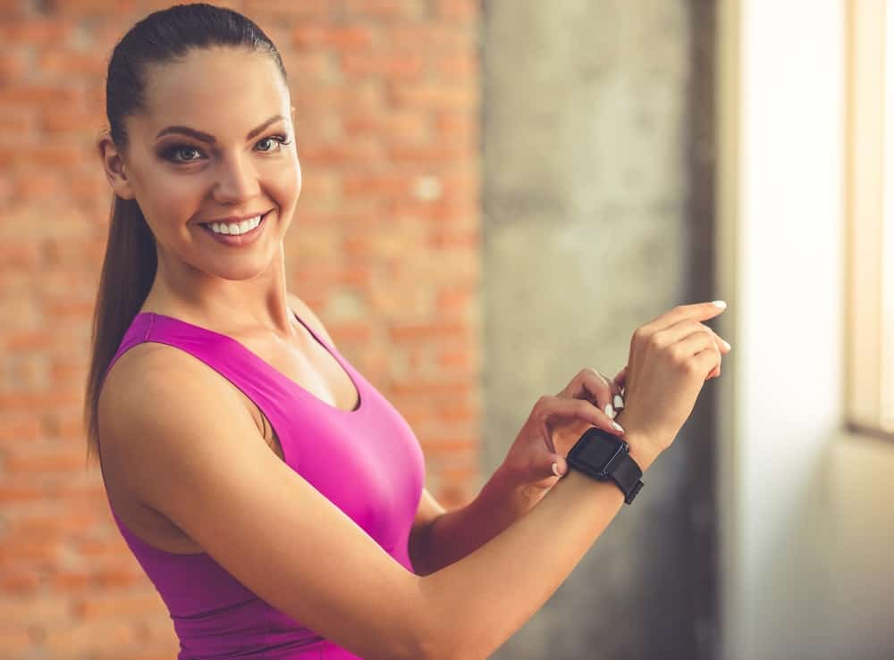 A woman adjusting her Fitbit before exercising.