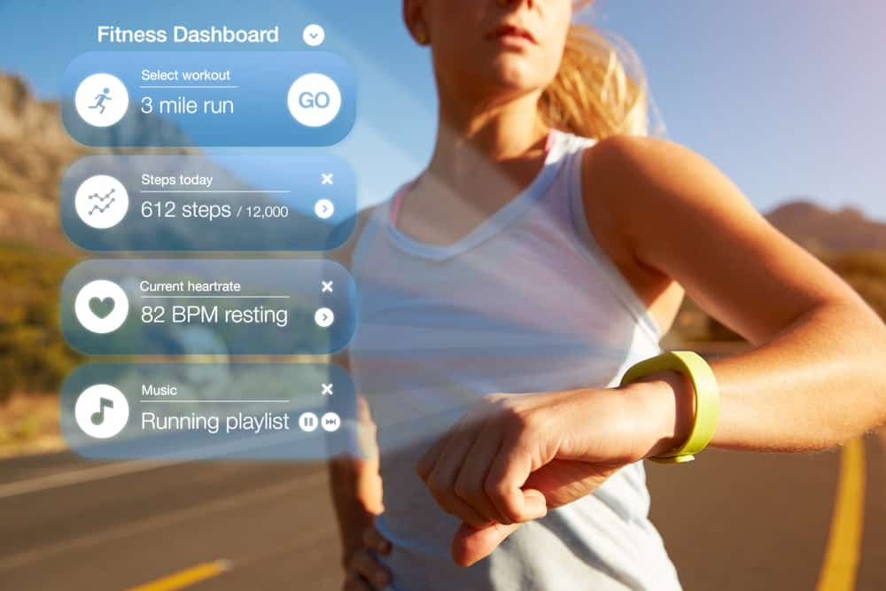 An exercising woman checking the notifications of her health tracker.