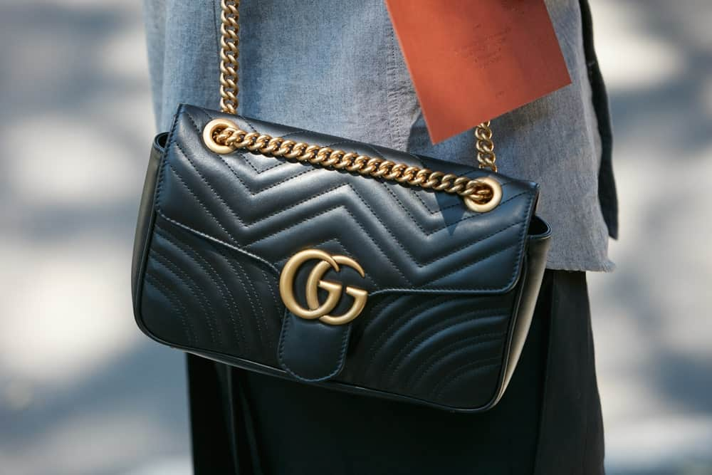 Woman with black Gucci leather bag.