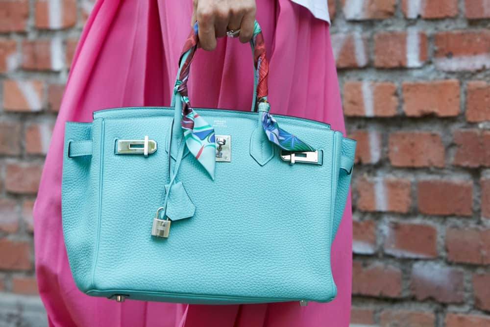 Woman with Hermes turquoise leather bag.