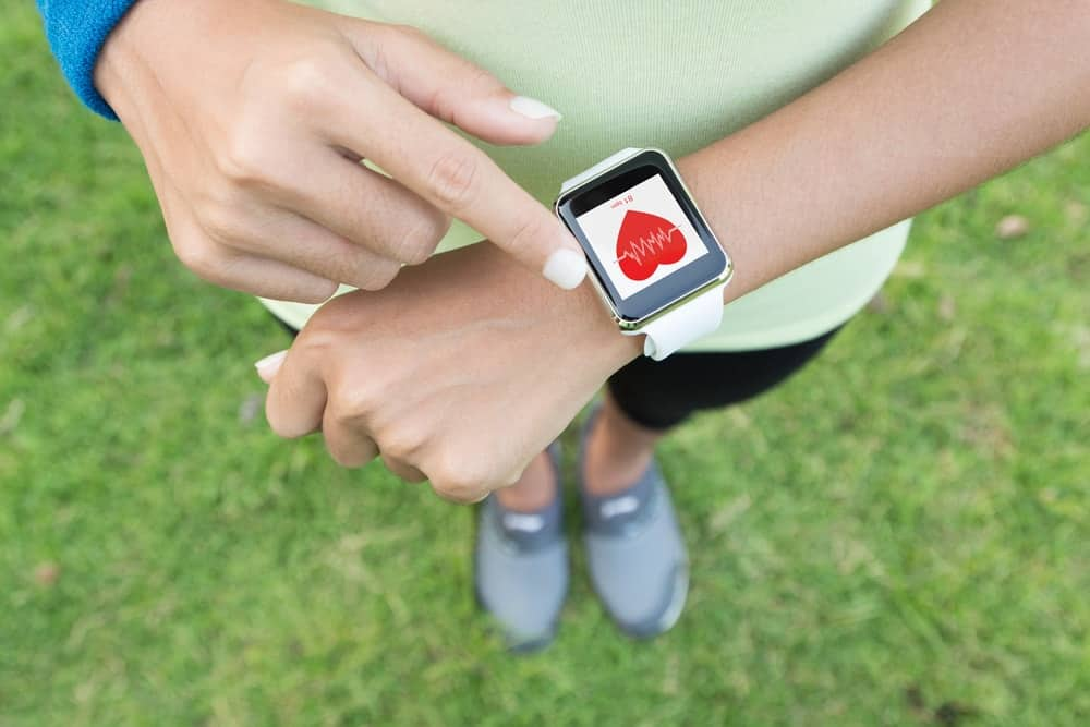 A sporty woman monitoring her heart rate with an Apple Watch.