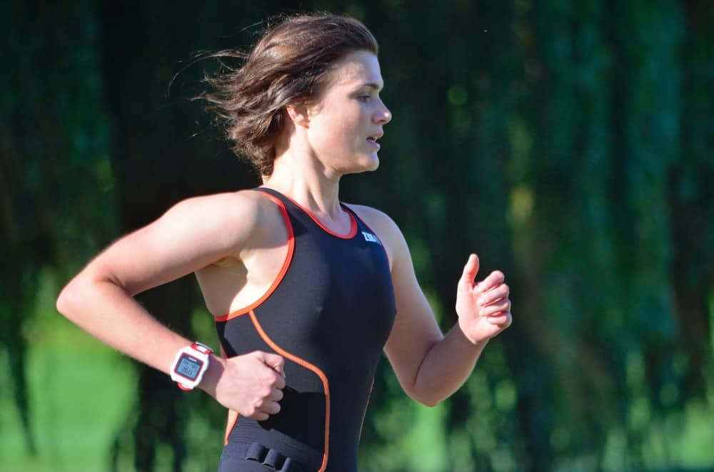 An athlete running with a Fitbit on.