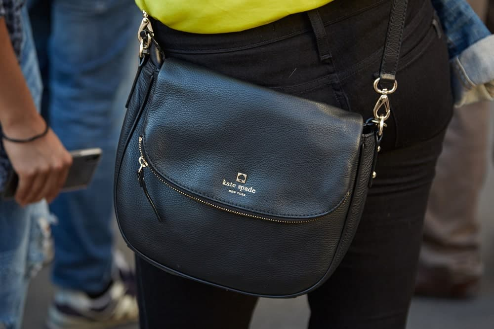 Woman with Kate Spade black leather bag.