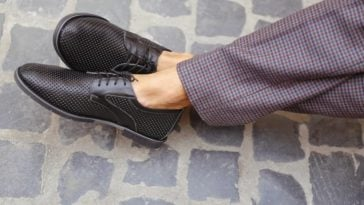 A close look at a man wearing a pair of checkered pants to match his summer shoes.