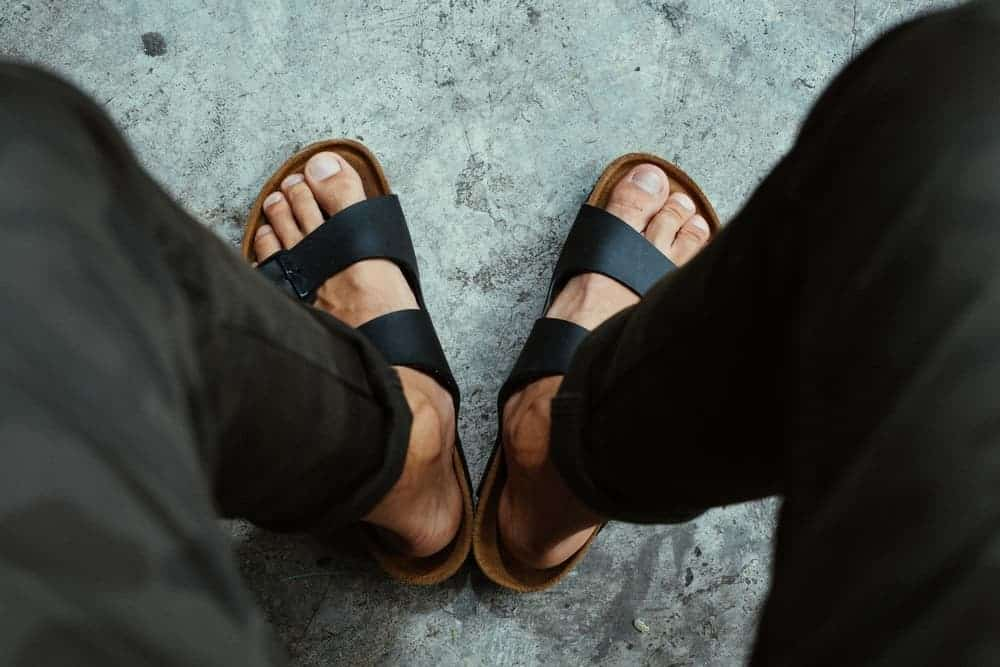 A man wearing a pair of strap sandals with his pants.