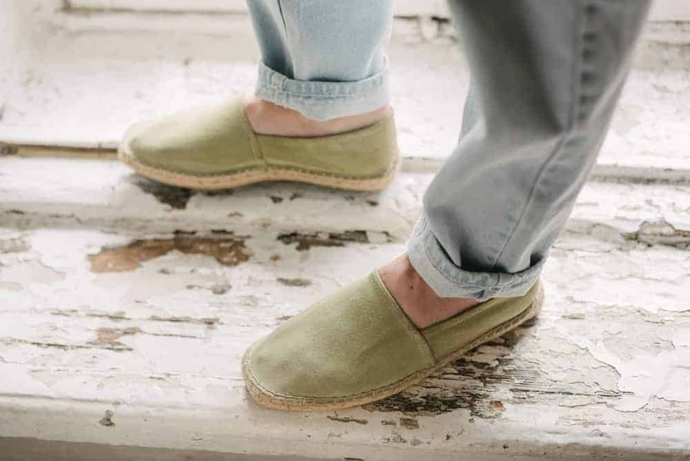 A man wearing a pair of green espadriller with his faded blue jeans.
