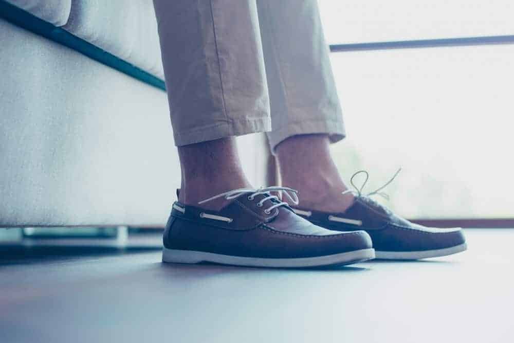 A man wearing a pair of khaki pants with his dark brown boat shoes.