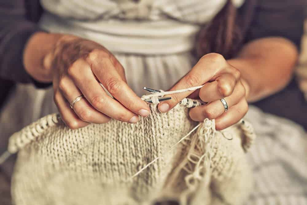 A close look at a woman knitting with yarn.
