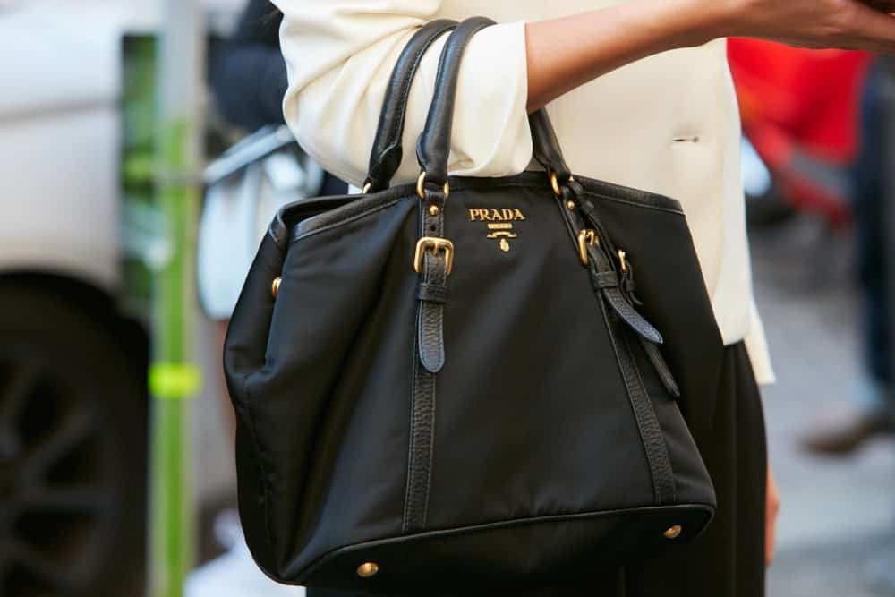 Woman carrying a black Prada bag.