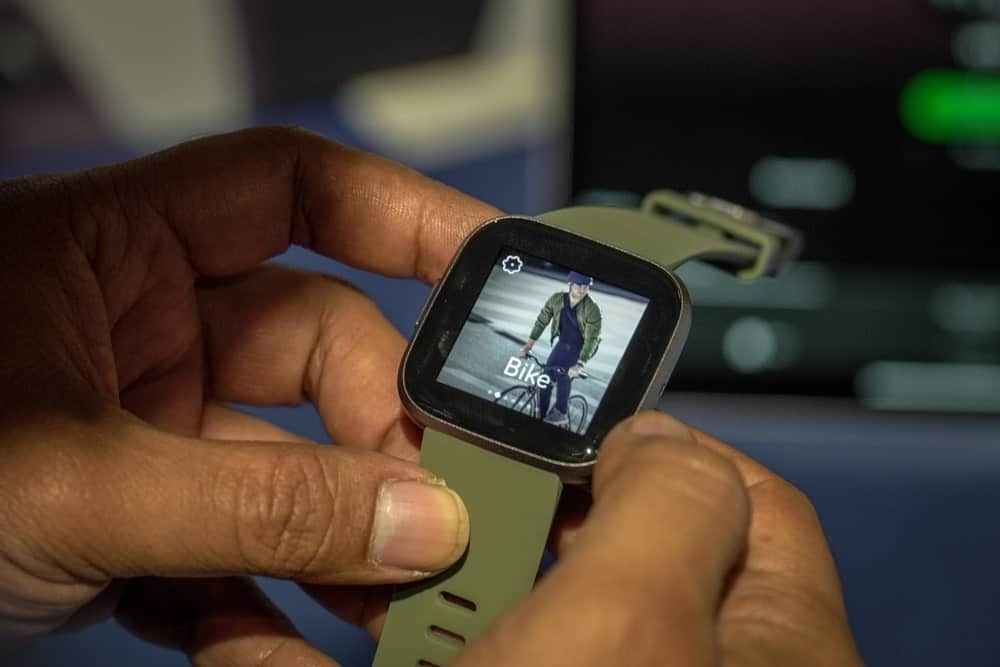 Hands holding a green Fitbit smartwatch.