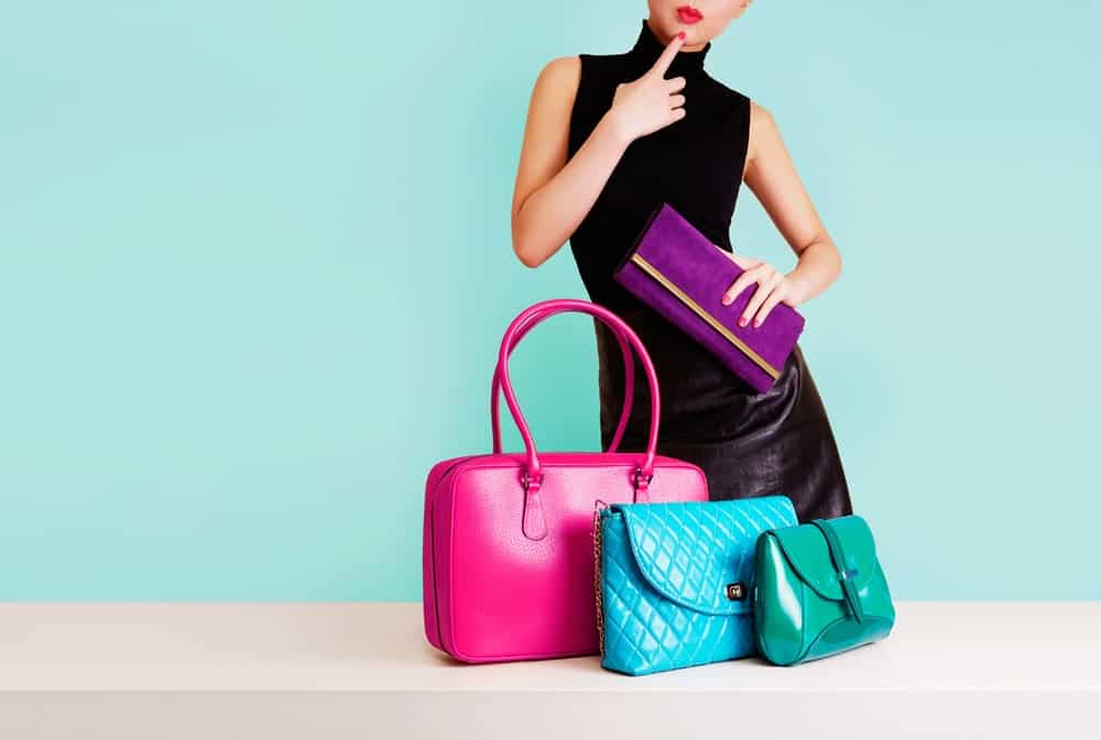 A woman deciding which purse or handbag to use.
