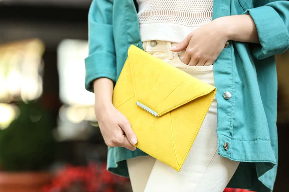 A close look at a woman carrying an envelope clutch.