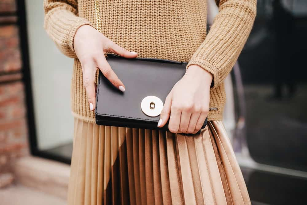 A close look at a woman carrying a black leather clutch bag.