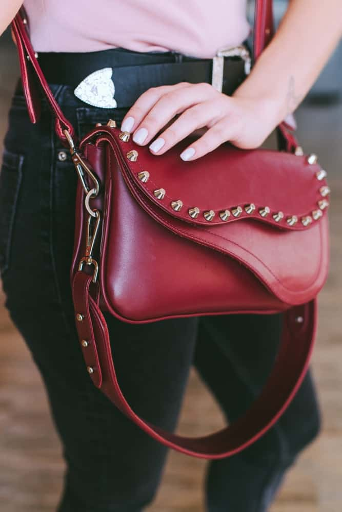 A woman sporting a red leather crossbody purse.