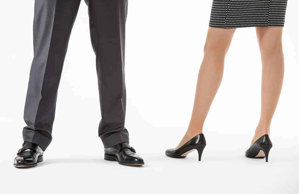 Man and woman's legs wearing black dress shoes.