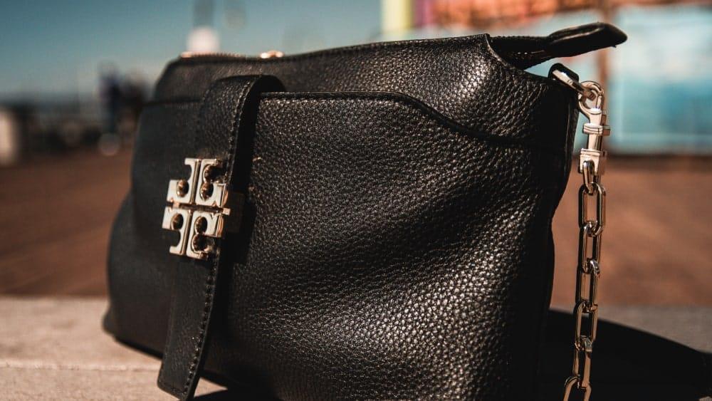 Black leather Tory Burch purse on display.