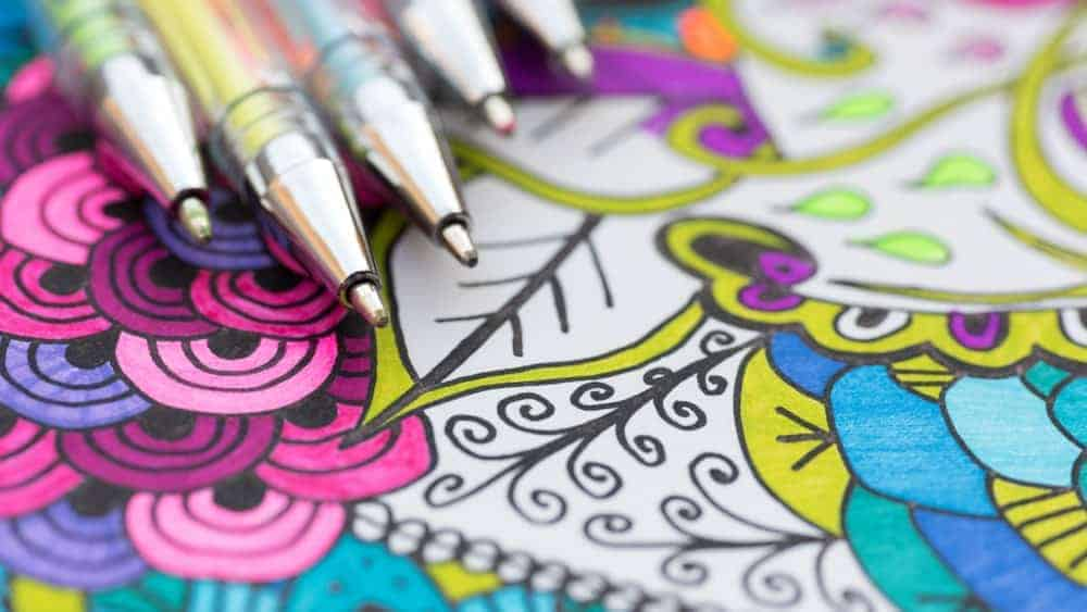 A close look at gel pens on a background of colorful illustrations.