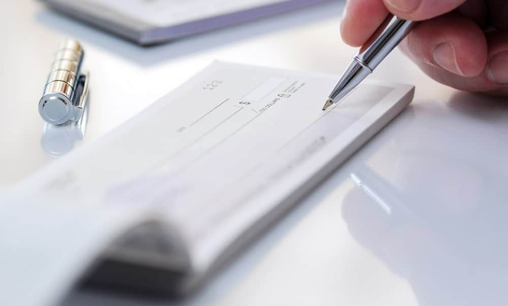 A close look at a person writing a check with the use of a check-safe pen.