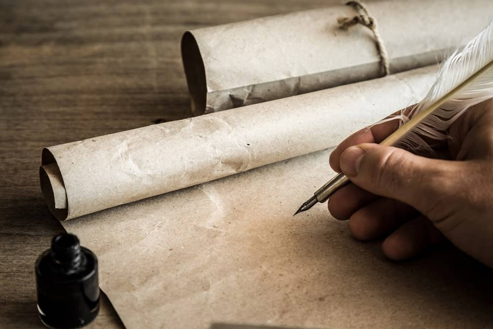 A feather quill pen being used to write on brown paper.