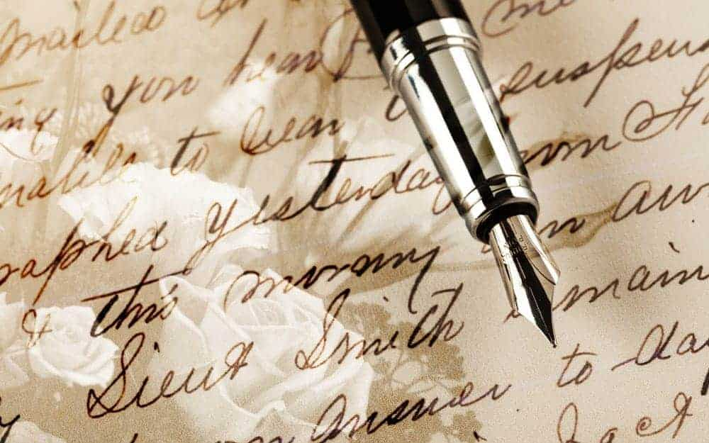 A close look at a fountain pen on a background of cursive words on paper.