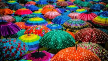 A look at a crowd of different colorful and patterned umbrellas under the rain.